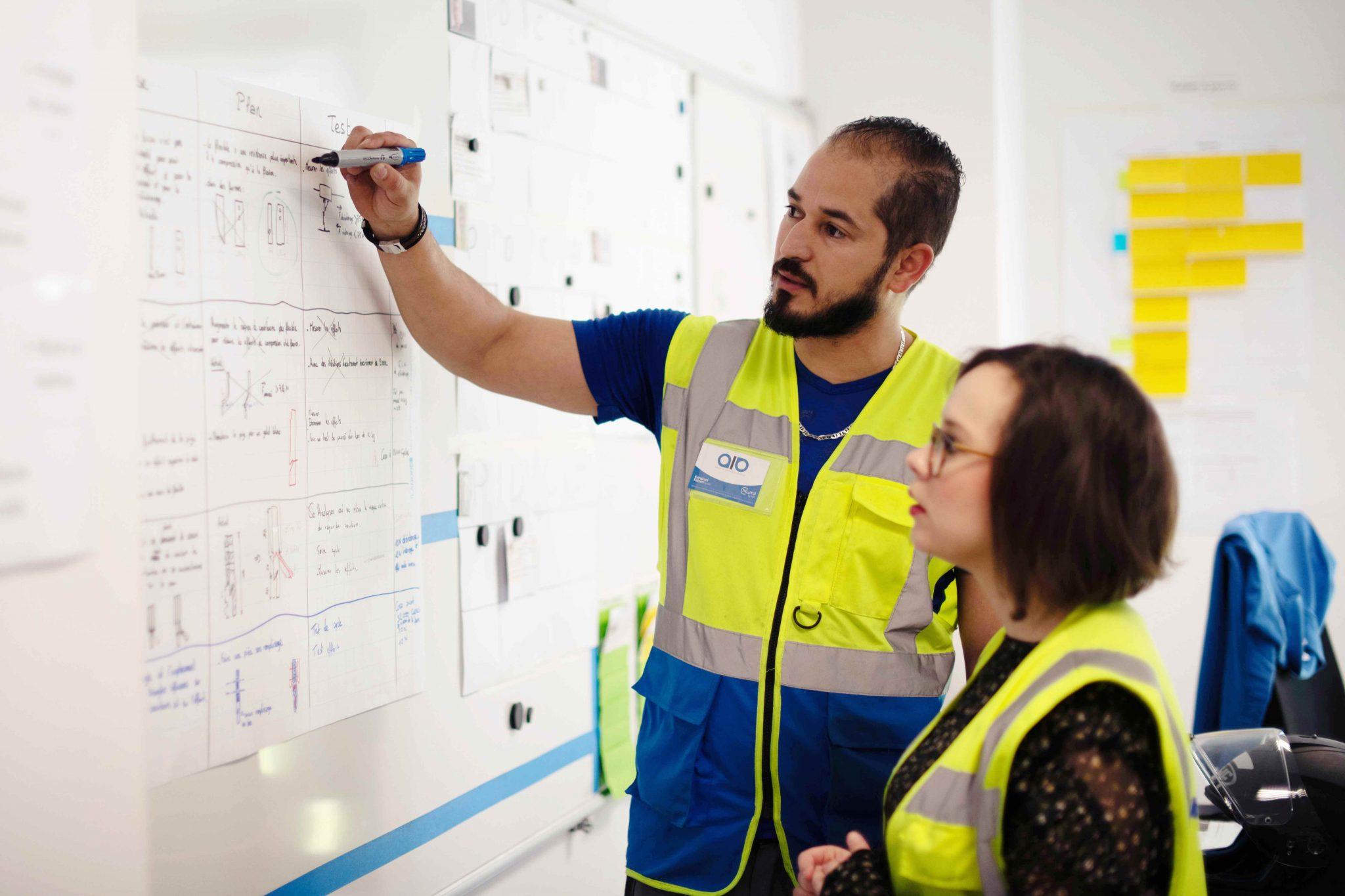 Engineer and technicien observing diagrams Karakuri Kaizen